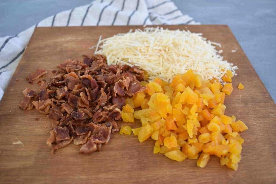 chopped bacon, dried apricots , and parmesan on cutting board