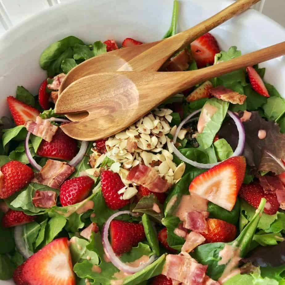 large white bowl of strawberry spinach salad with strawberry vinaigrette