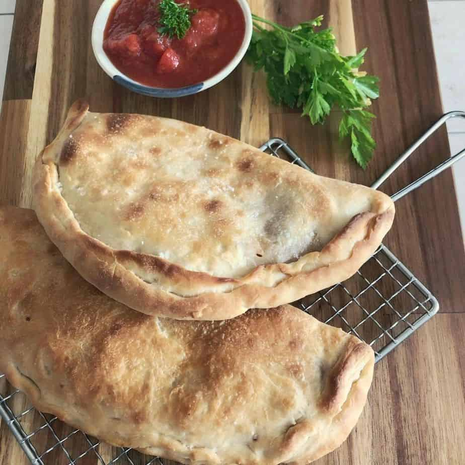 2 baked calzones with marinara sauce