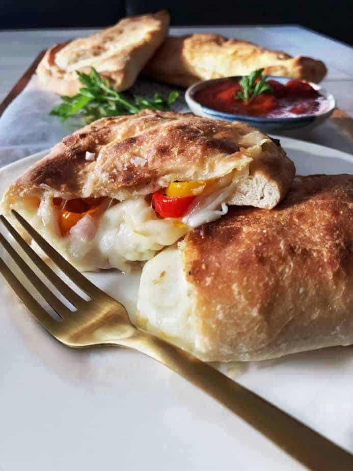 Calzone cut open with filling and fork.