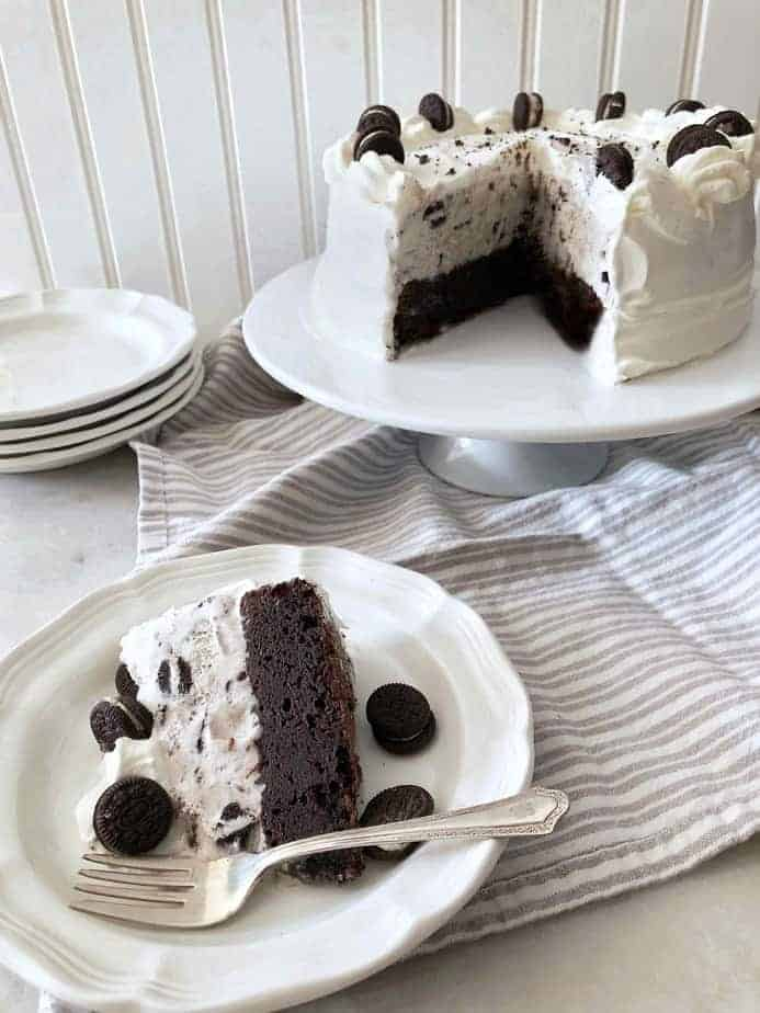 cake plate with slice of Oreo ice cream cake and full cake behind