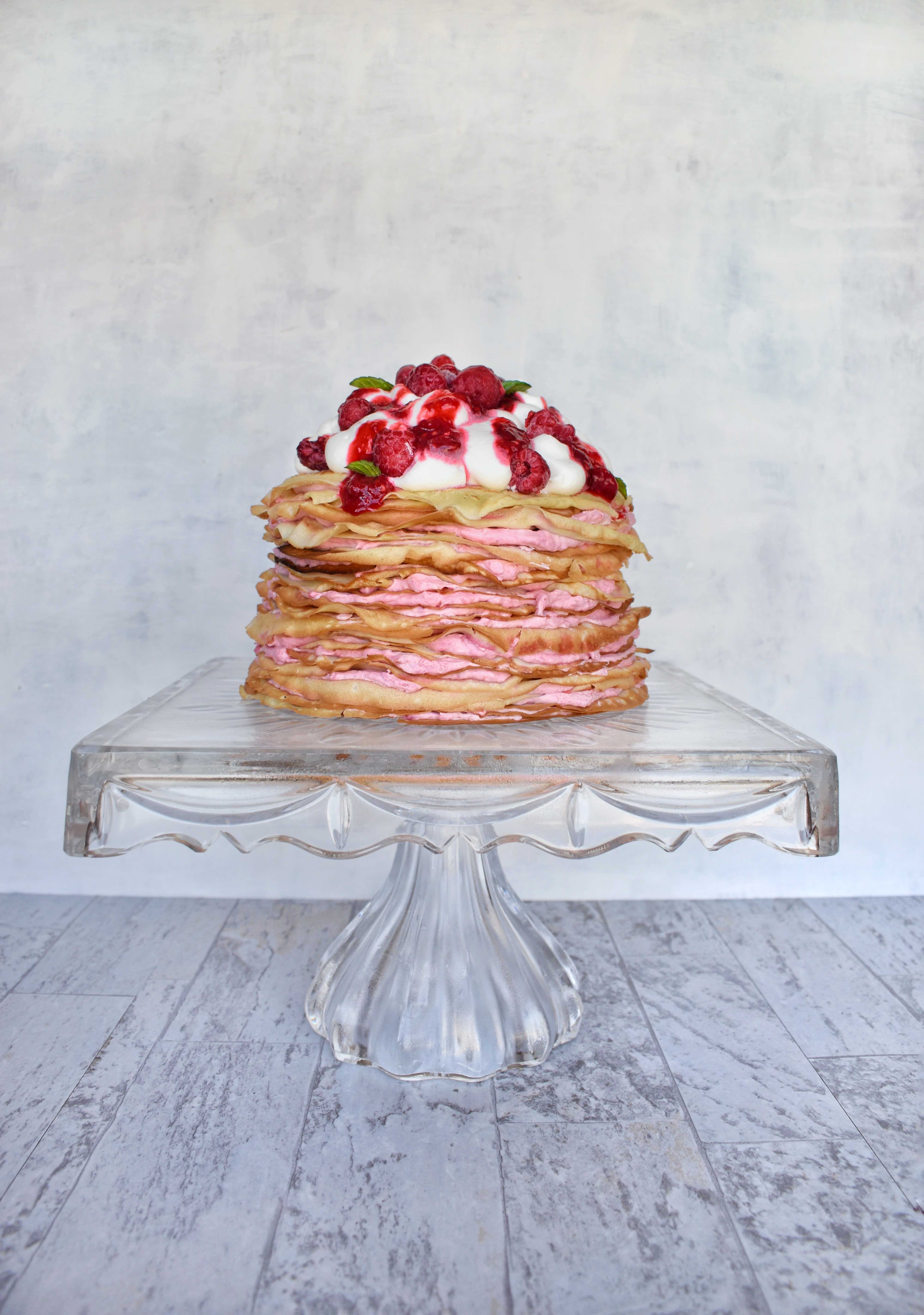 raspberry cream crepe cake on clear glass pedestal