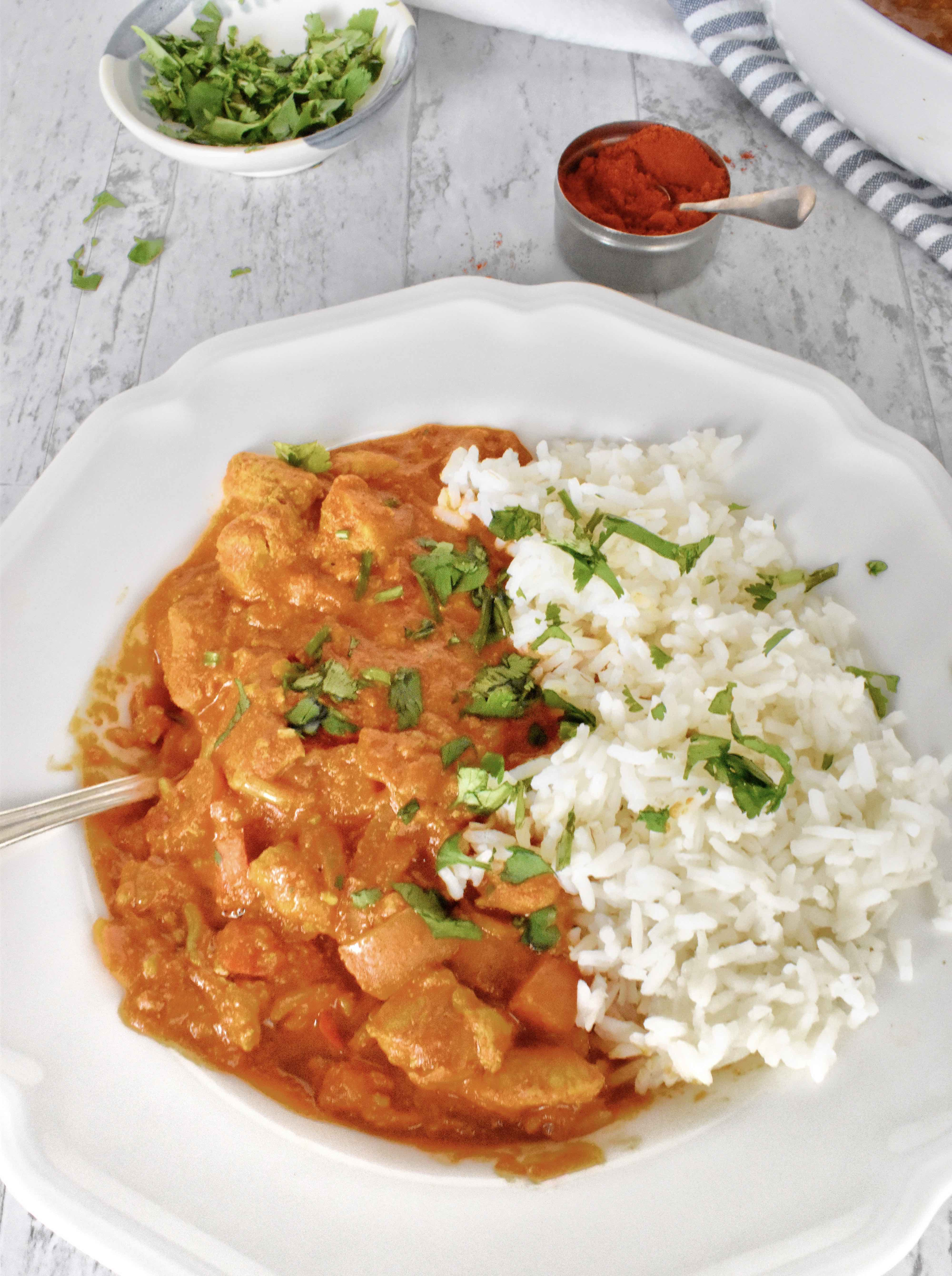 Chicken tikka masala in bowl with rice and cilantro garnish