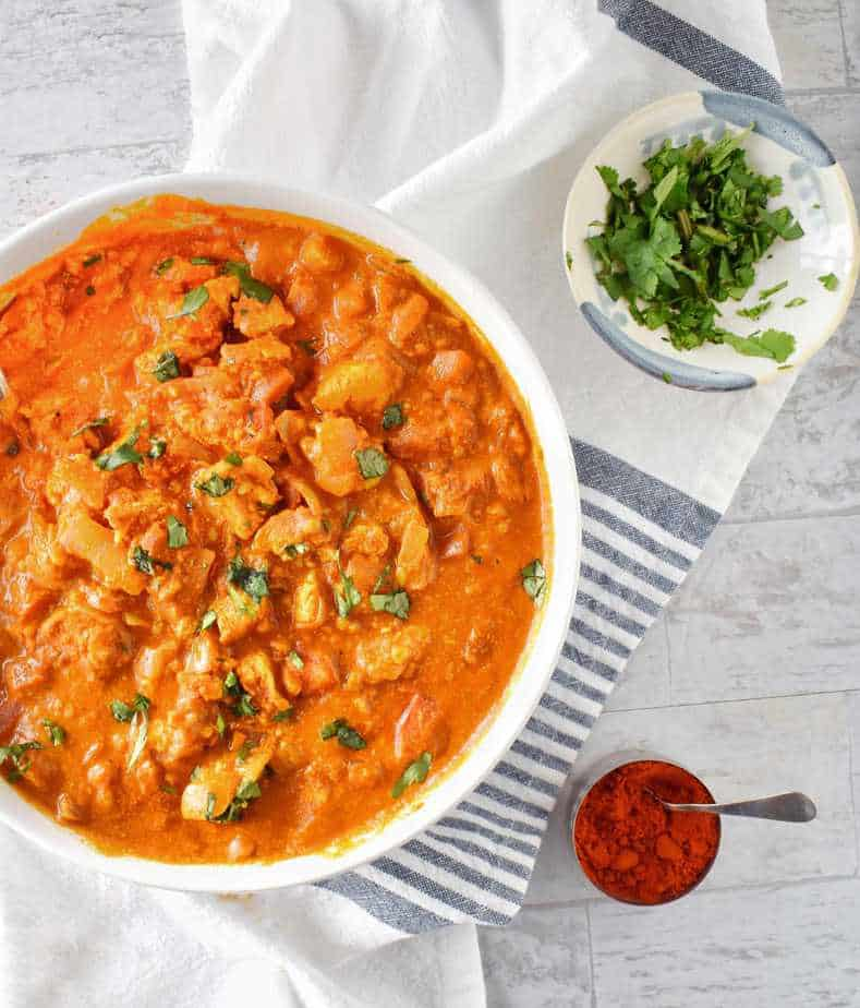 chicken tikka masala in a large bowl with chili and cilantro on the side