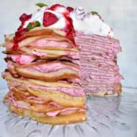 Raspberry cream crepe cake with slice missing