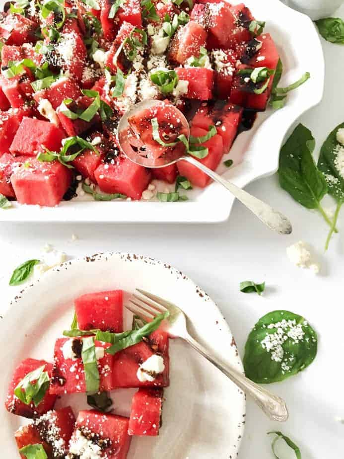 watermelon, feta, basil salad on white platter and salad plate