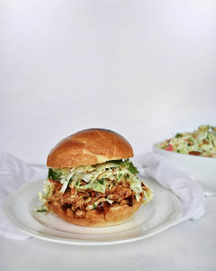 coleslaw on a pulled pork sandwich on a white plate