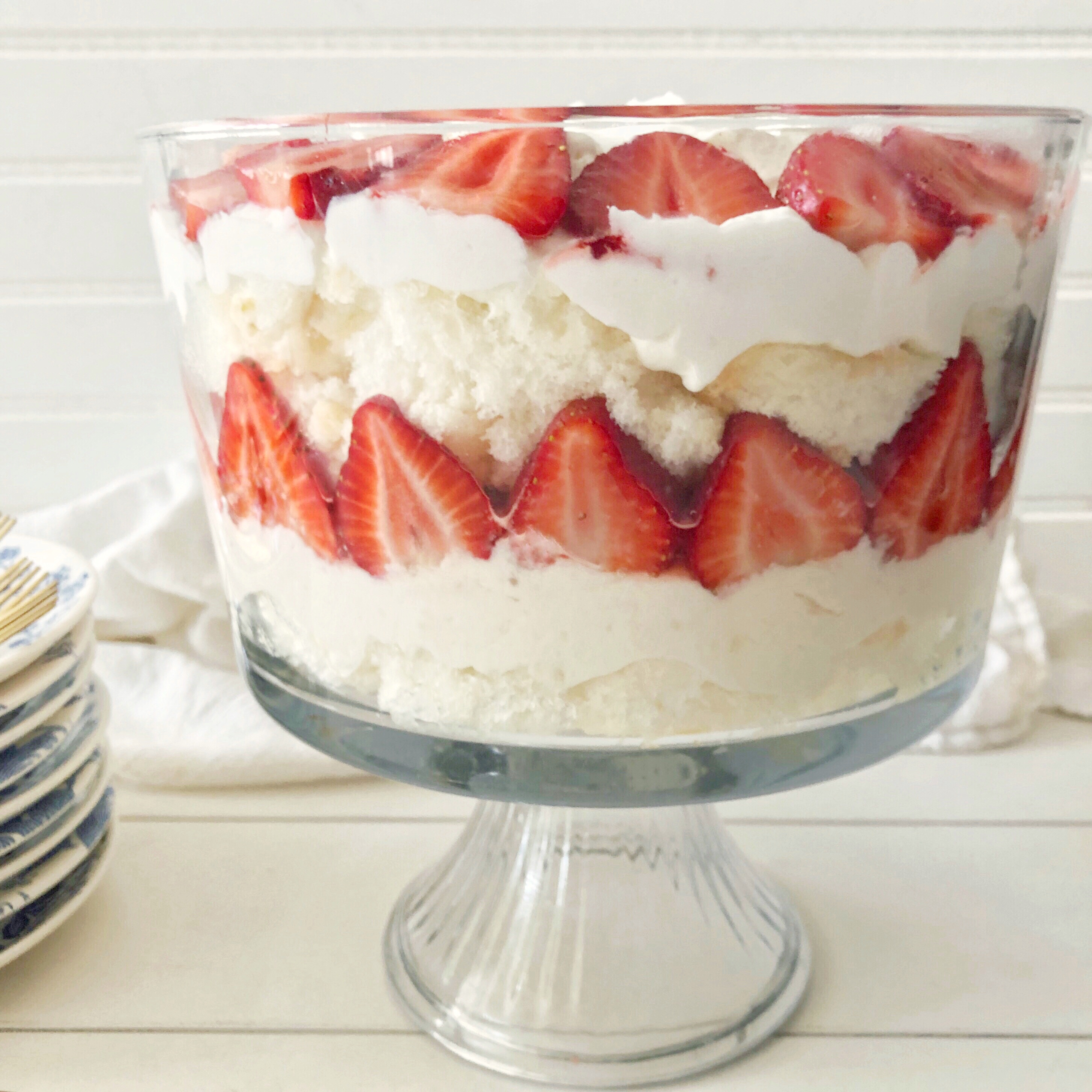 strawberry lemon trifle layered in a footed glass bowl