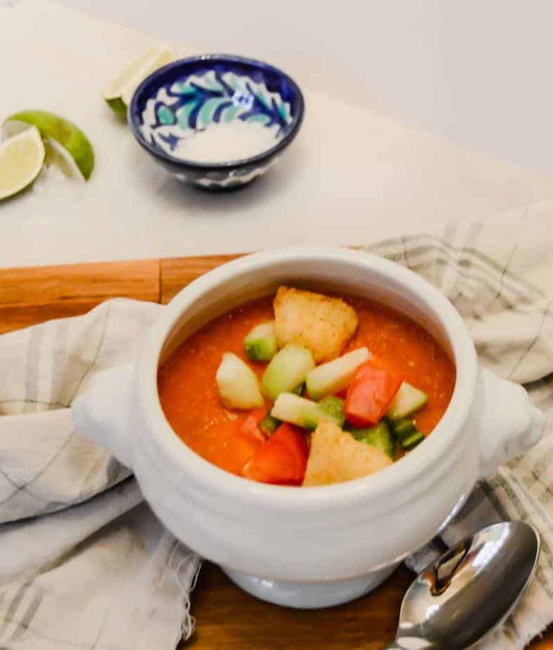 bowl of red Gazpacho Spanish soup topped with cucumber, peppers and croutons