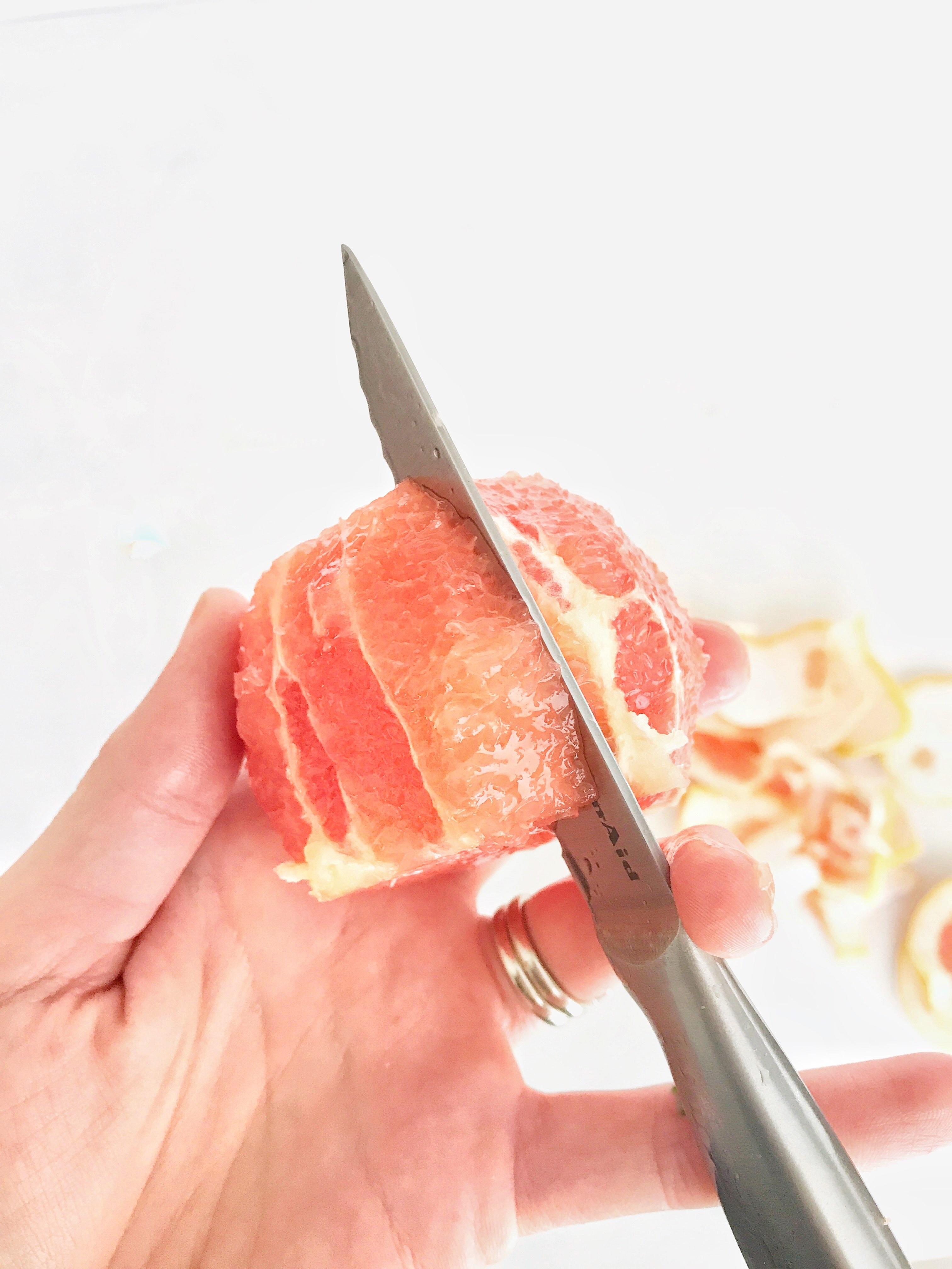 slicing in between segments of the grapefruit