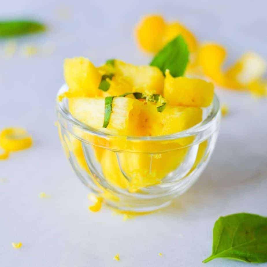 summer salad of pineapple, lemon & basil in glass cup.