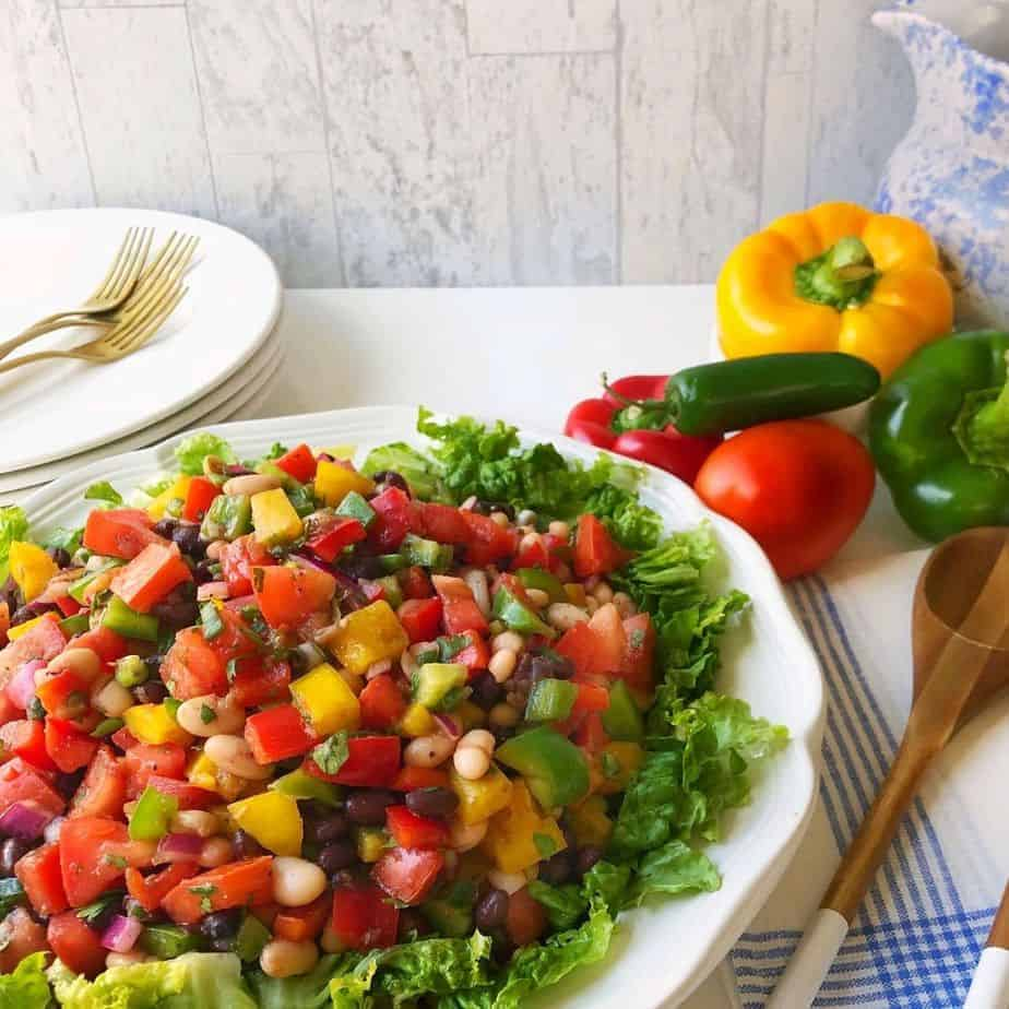 healthy black and white bean salad with colorful vegetables on white platter.