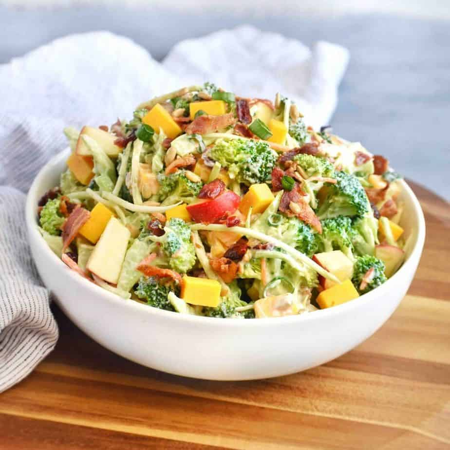 broccoli salad in white bowl on wooden board.