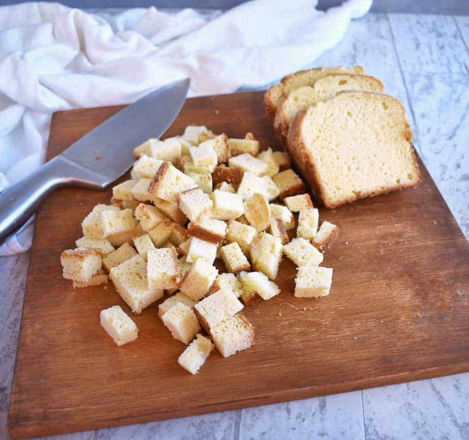 pound cake cut up into bite size pieces on a wooden cutting board