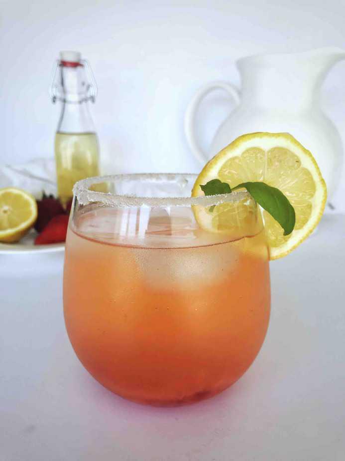 glass of strawberry basil lemonade with lemon slice on rim