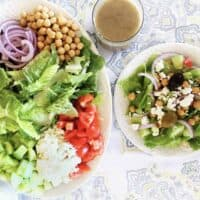 Greek salad on a platter with tossed salad on small plate and jar of vinaigrette