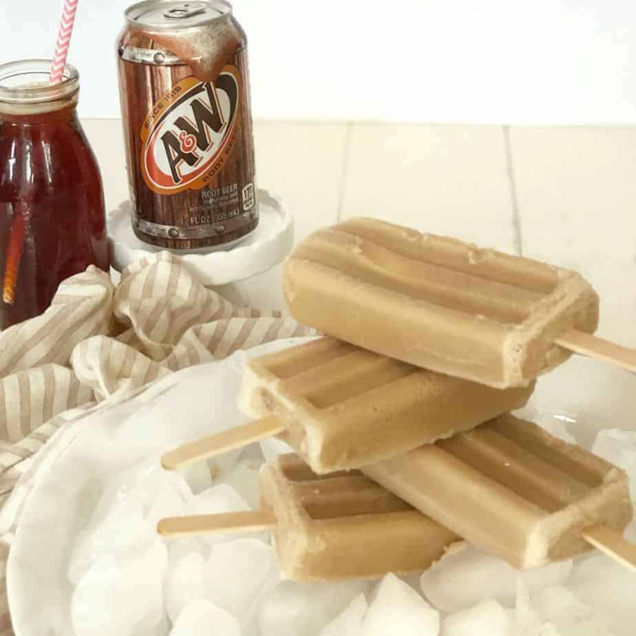 stack of root beer float popsicles on ice with A & W root beer can and glass