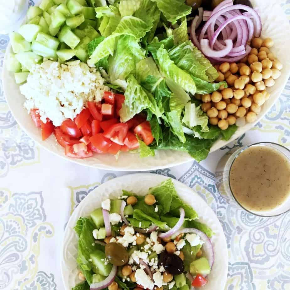 large and small white plates of greek salad. featured image
