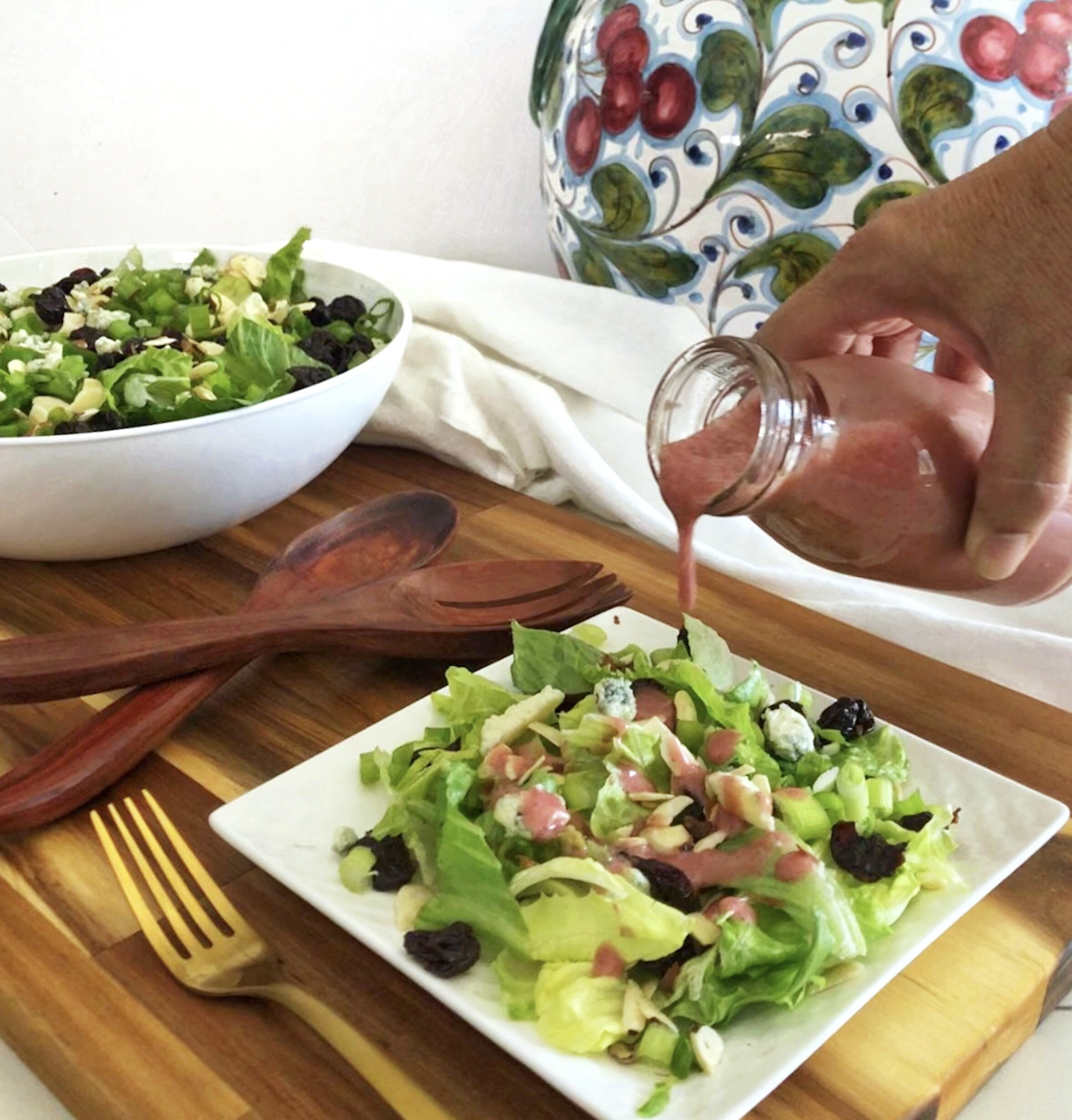 cherry vinaigrette pouring over cherry salad with gorgonzola and toasted almonds