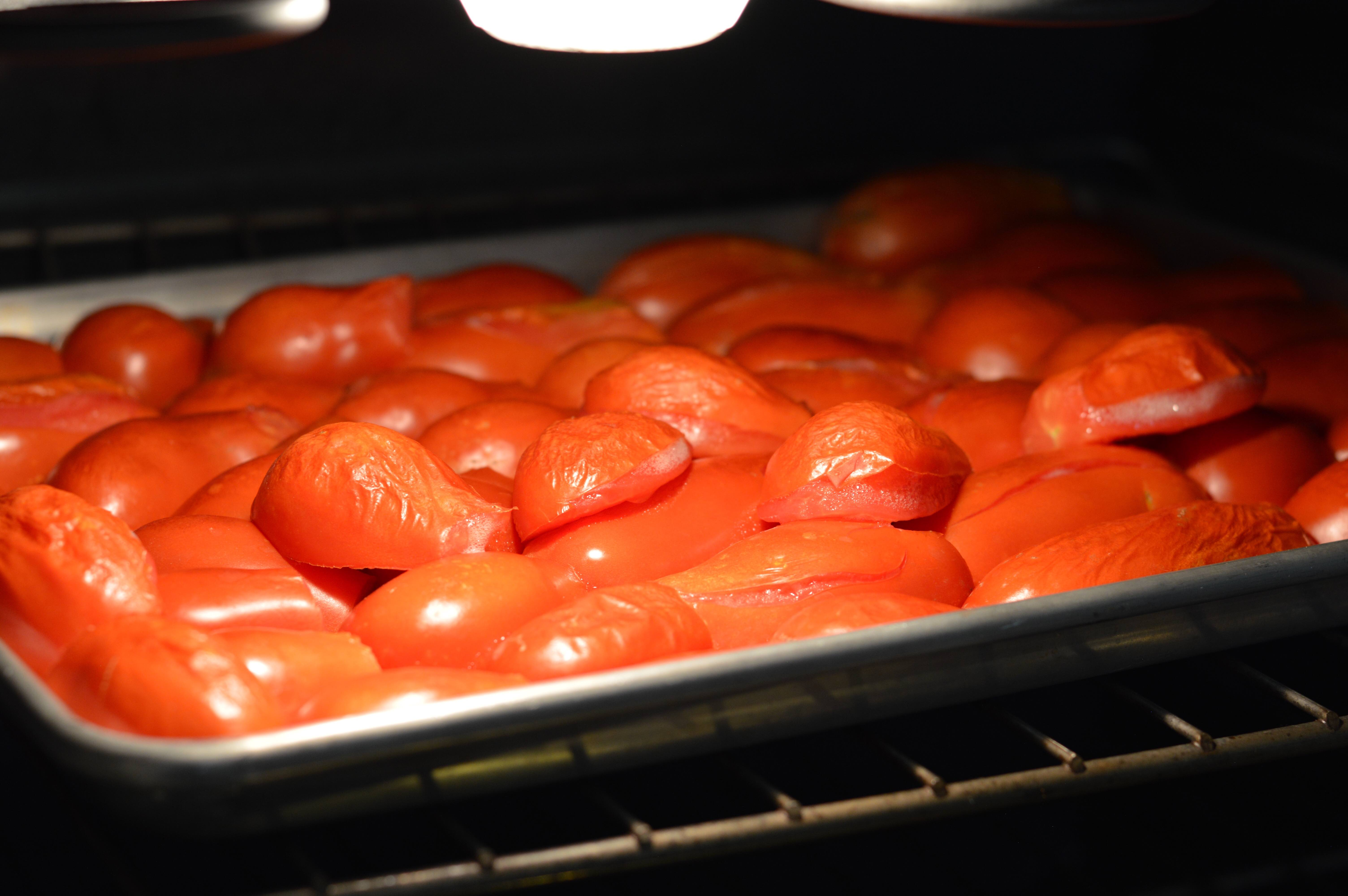 baking sheet of tomato halves broiling in oven
