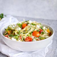 white bowl with zucchini noodle pasta toped with tomatoes and fresh herbs