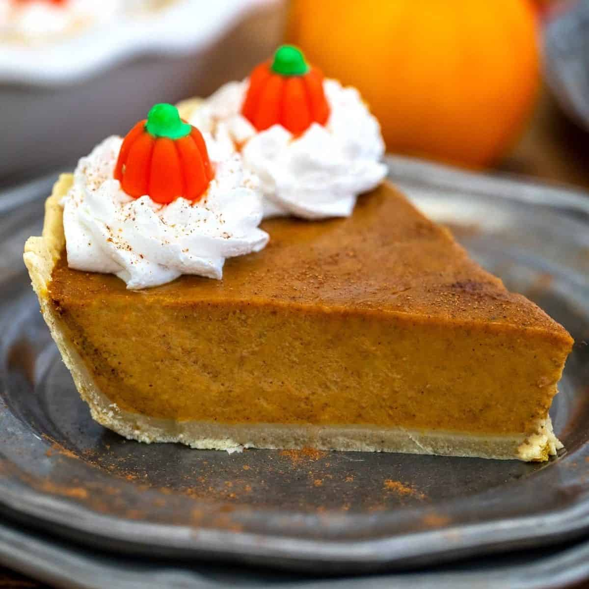 slice of pumpkin pie with whipped cream and little candy pumpkins on top.