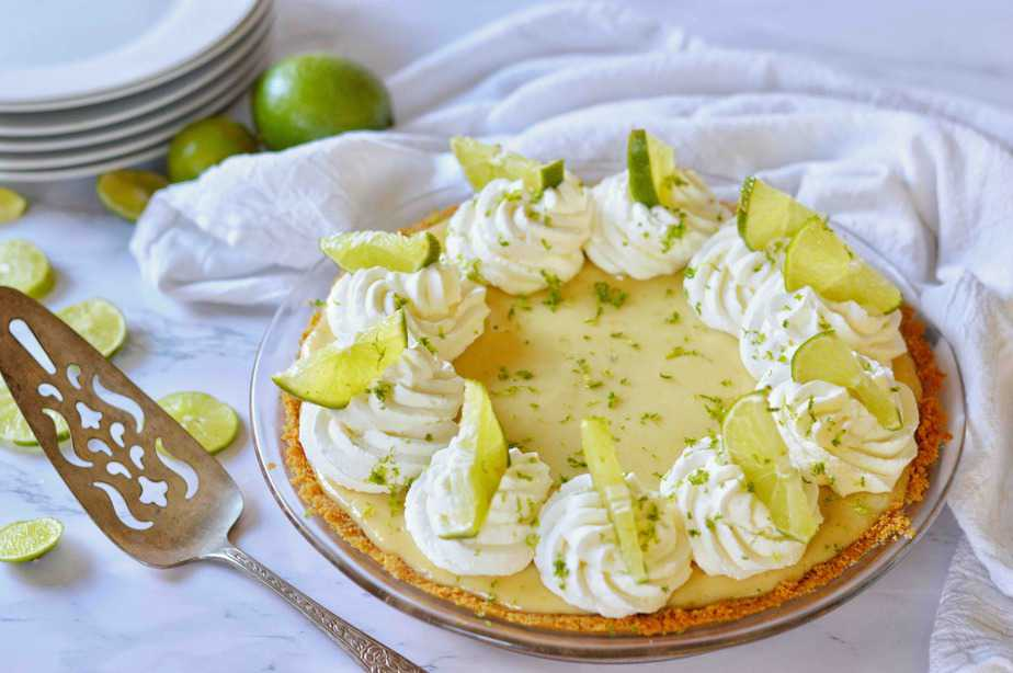 key lime pie w pie server and stack of plates