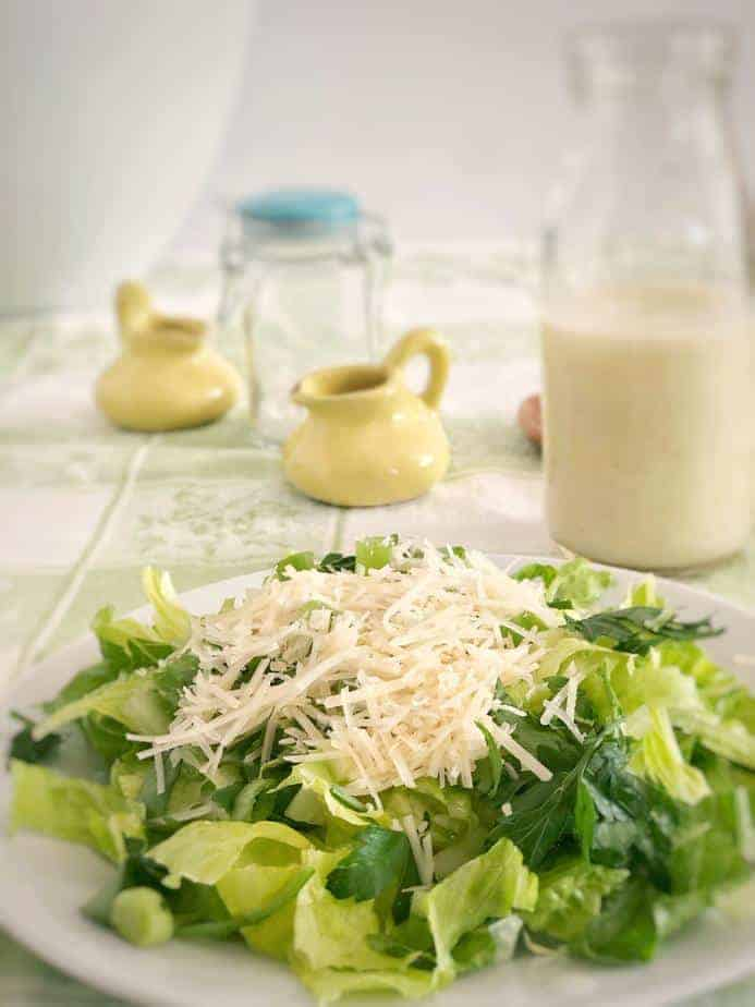 plate of Sensation Salad with two little yellow pitchers and bottle of dressing