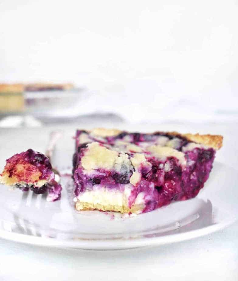 blueberry pie slice on plate with fork and bite out of it