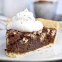 slice of chocolate pecan pie with whipped cream on top