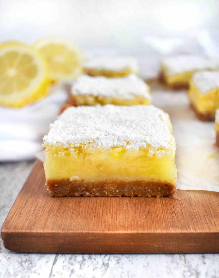 lemon bar on wooden board with lemons in back