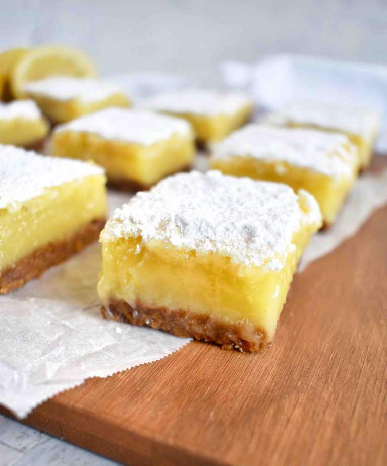 lemon bars in a row on a wooden platter