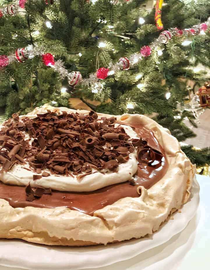 chocolate meringue torte sits in front of Christmas tree