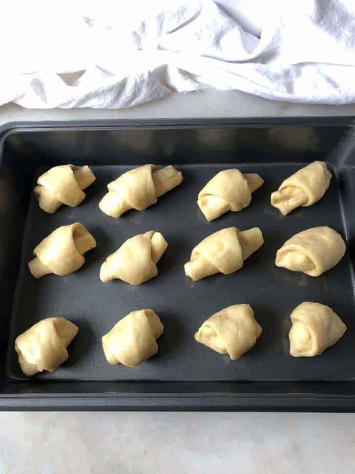 baking sheet with ham and cheese rolls ready to bake