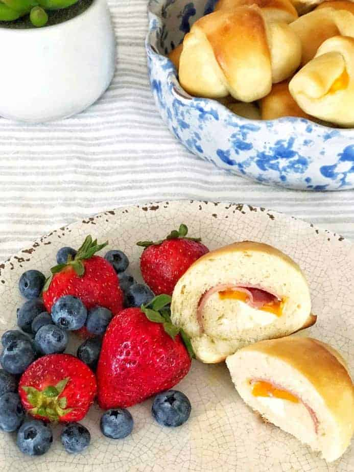 bowl of rolls and plate with cut open ham and cheese rolls and berries