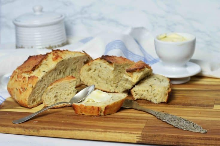Herb Artisan Bread sliced on cutting board with butter