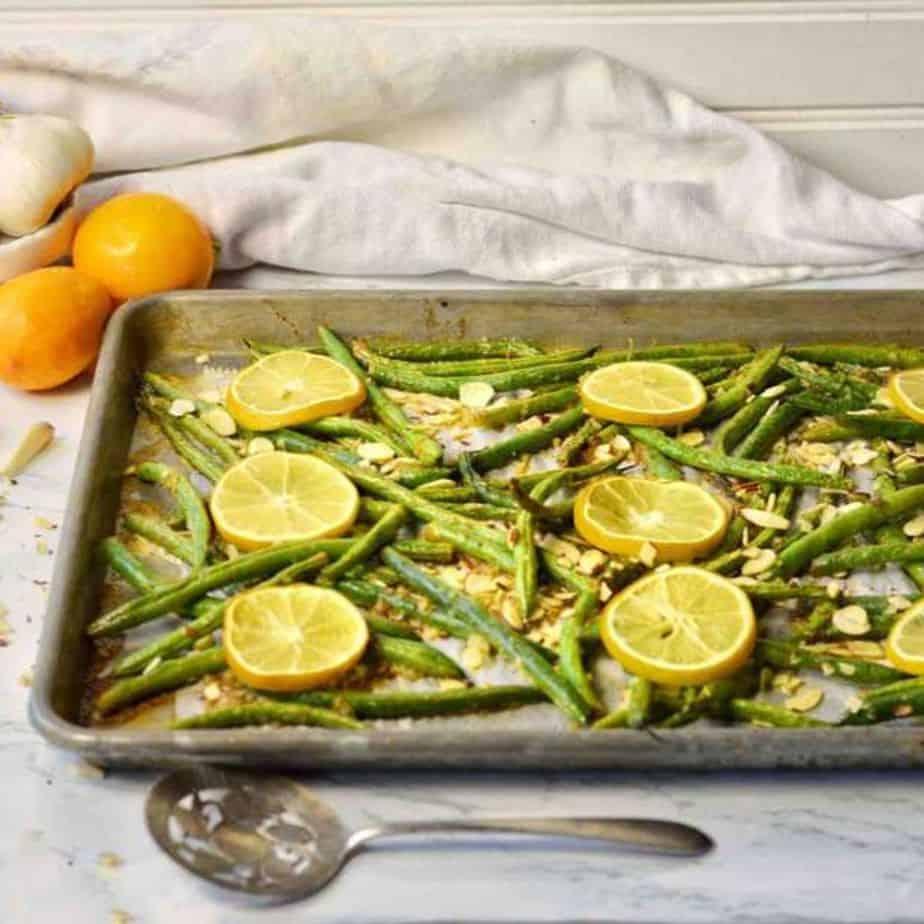 green beans with lemon slices on baking sheet.