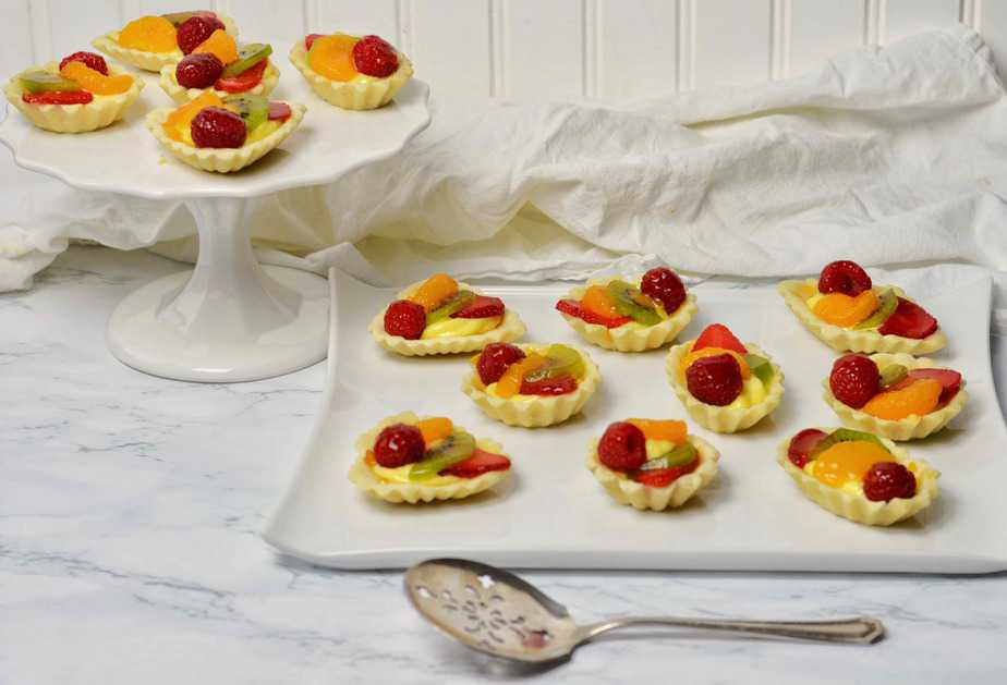 fresh fruit tarts atop white platters are ready to serve