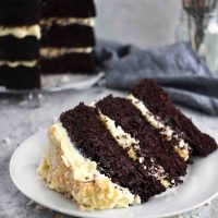 slice of chocolate coconut torte cake with full cake in background