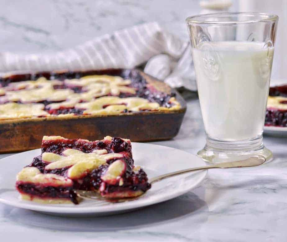 slice and whole pan of Triple Berry Slab pie with milk