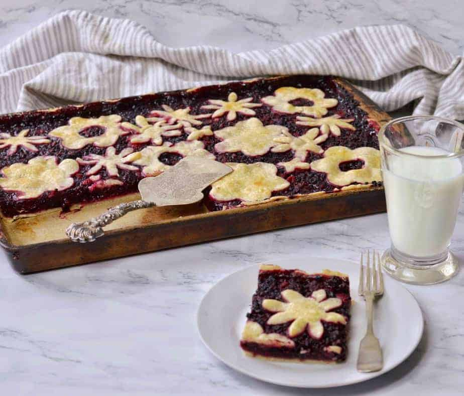 slice of triple berry slab pie with fork and glass of milk