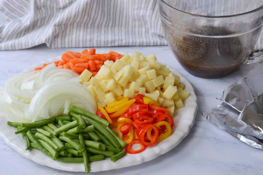 Cut vegetables and marinade for foil dinners