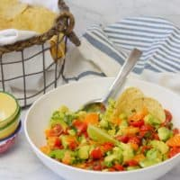white bowl of mandarin guacamole with basket of tortilla chips