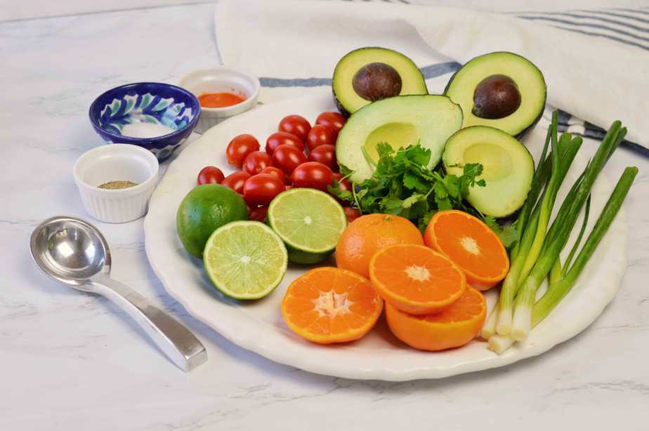white platter of fresh ingredients for mandarin guacamole