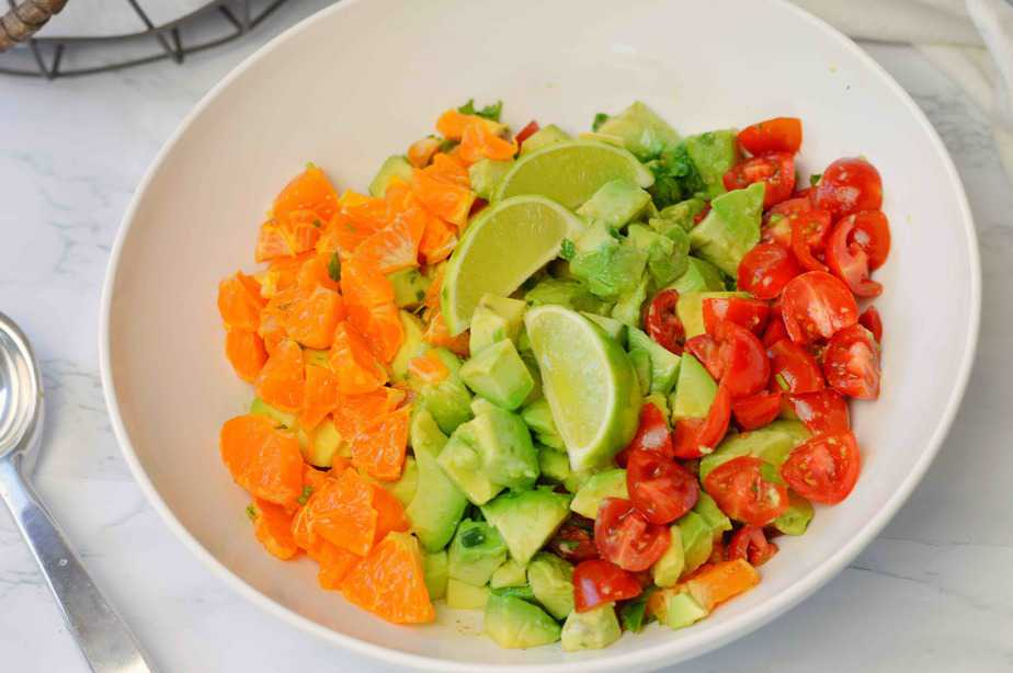 white bowl with chopped mandarin oranges, avocados, tomatoes and green onion for mandarin guacamole