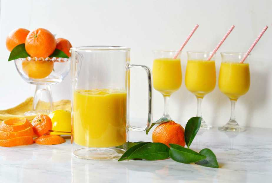 orange mango freeze in glasses and pitcher with tangerines