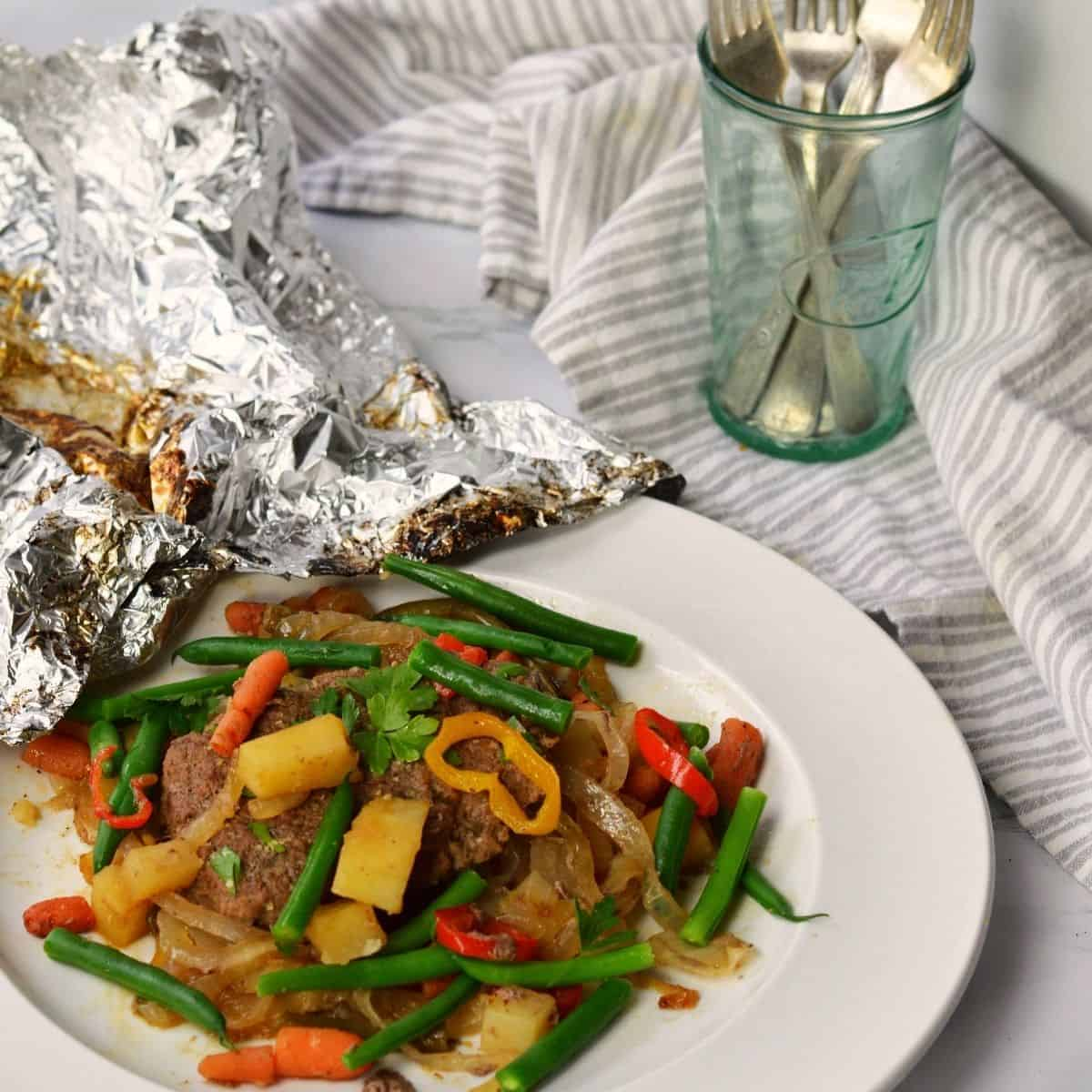 Ground beef patty with vegetables on plate and foil behind
