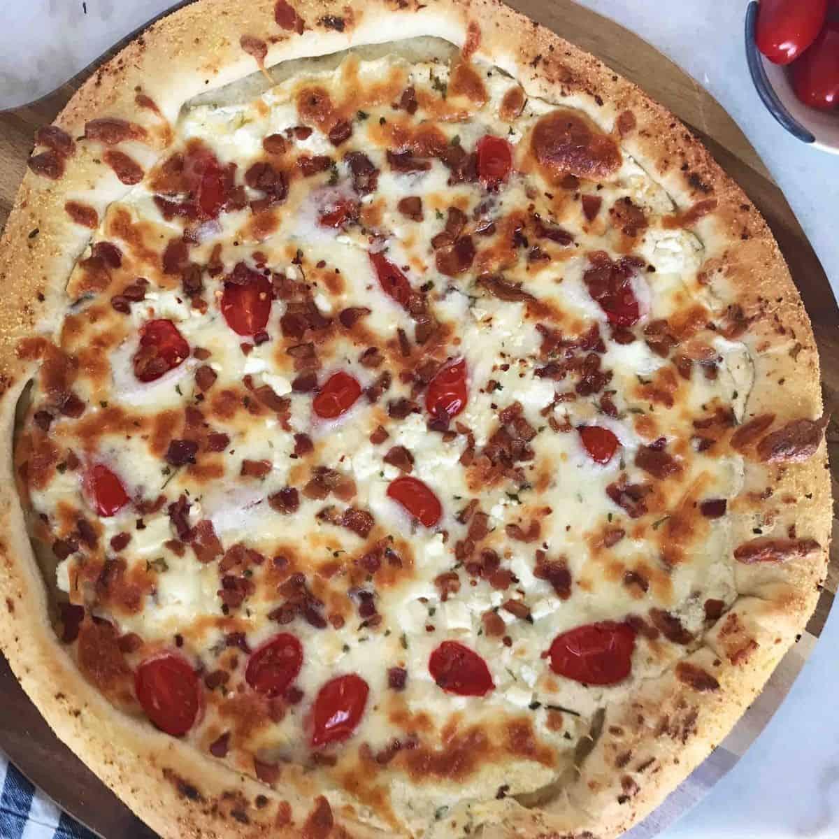 full pizza on wooden board.