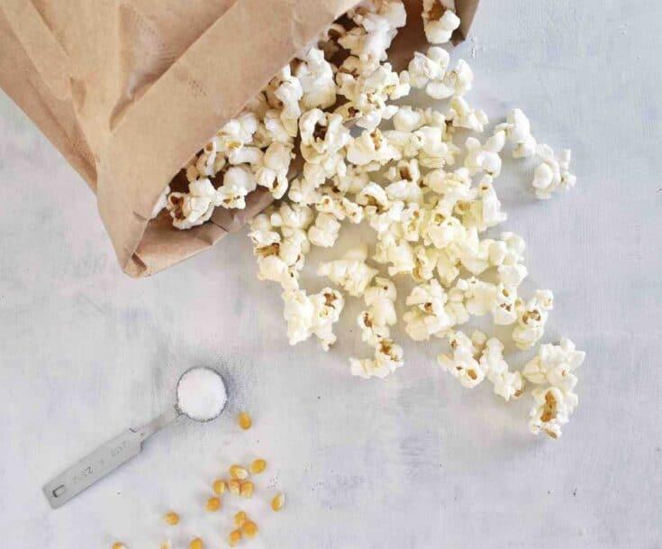 popcorn spilling out of paper bag with salt and popcorn kernels