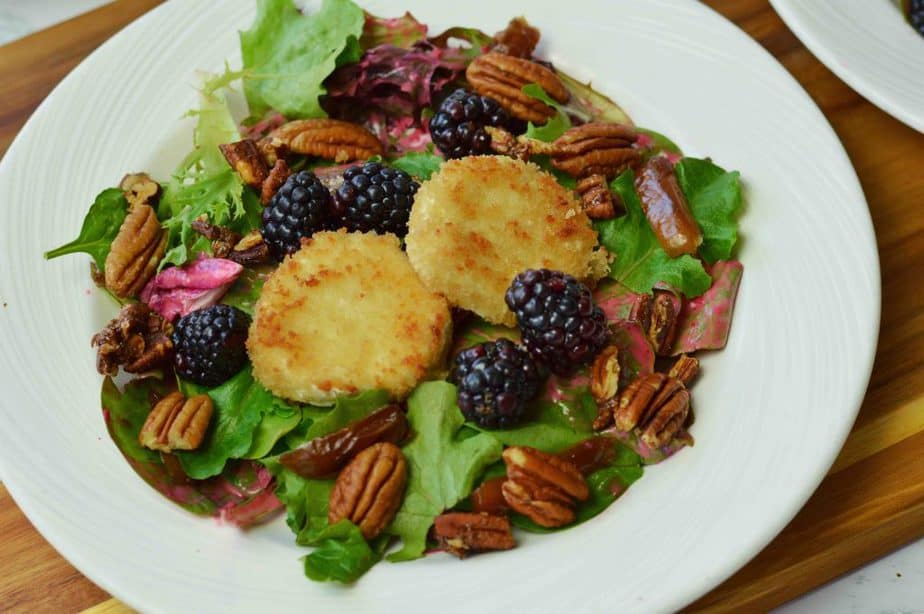 warm goat cheese and spiced pecan salad on white plate